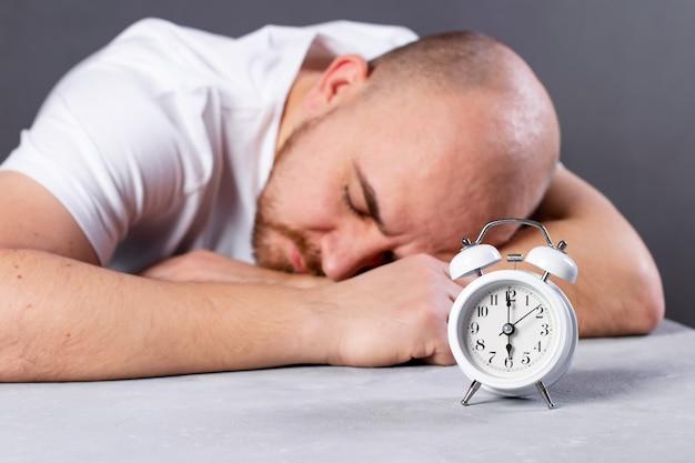 Erschöpfter männlicher arbeiter, der mit wecker am tisch schläft, mann arbeitet von zu hause aus