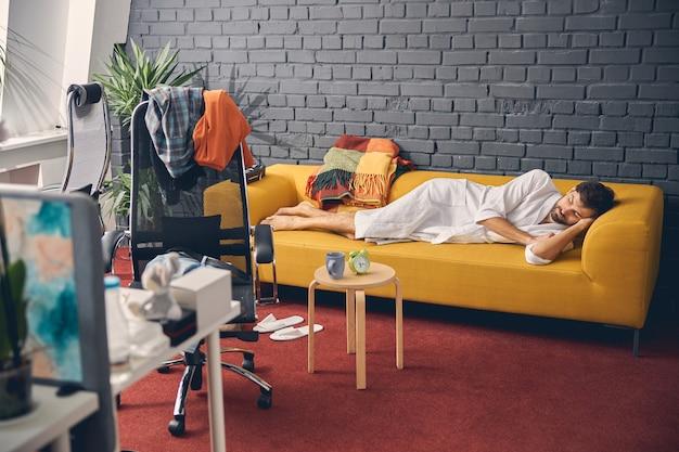 Erschöpfter männlicher arbeiter im weißen bademantel, der auf dem sofa im modernen büro ein nickerchen macht