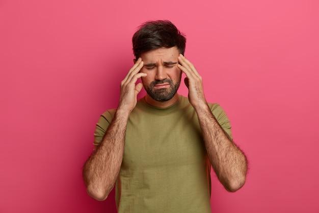Erschöpfter mann berührt schläfen mit geschlossenen augen, leidet unter kopfschmerzen, wartet darauf, dass jemand schmerzmittel mitbringt, trägt ein t-shirt, hat einen schlechten tag, ist über einer rosa wand isoliert und leidet unter schmerzhaften krankheiten