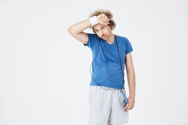Erschöpfter mann, der sich nach dem training die stirn mit einem schweißband abwischt