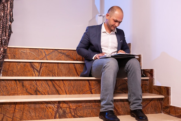 Erschöpfter müder geschäftsmann, der professionelles deadling-finanzbericht liest. unternehmer, der spät abends arbeitet, sitzt auf der treppe im baubüro.