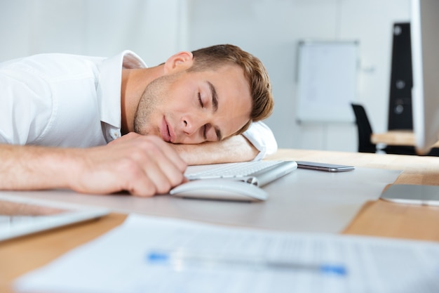 Erschöpfter, müder junger geschäftsmann, der im büro auf dem tisch schläft