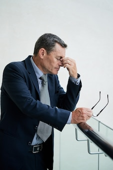 Erschöpfter reifer kaukasischer geschäftsmann mit geschlossenen augen, der sich den nasenrücken reibt, während er nach langem tragen der brille augenermüdung verspürt