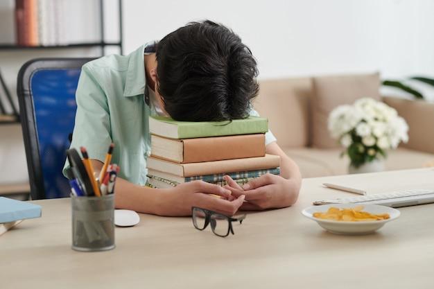 Erschöpfter teenager, der zu hause mit seinem kopf auf einem stapel büchern am schreibtisch sitzt, nachdem er für die prüfung studiert hat