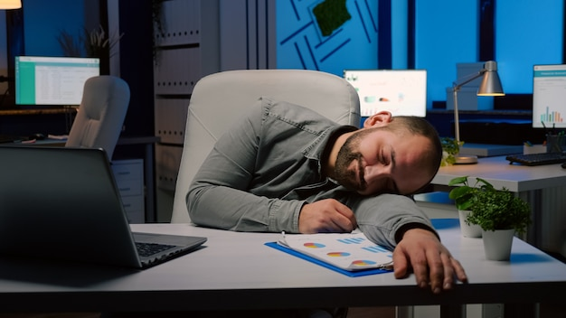 Erschöpfter überarbeiteter geschäftsmann, der auf schreibtischtisch im startup-geschäftsbüro schläft