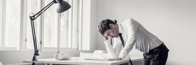 Erschöpfter und frustrierter geschäftsmann, der pläne oder blaupausen am schreibtisch in einem modernen büro analysiert.