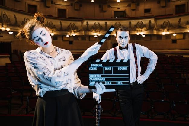Erschöpfter weiblicher pantomimekünstler, der clapperboard vor männlichem pantomimen hält