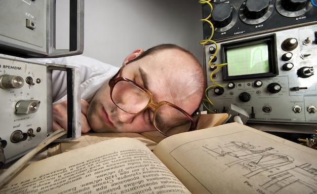 Erschöpfter wissenschaftler, der auf buch schläft