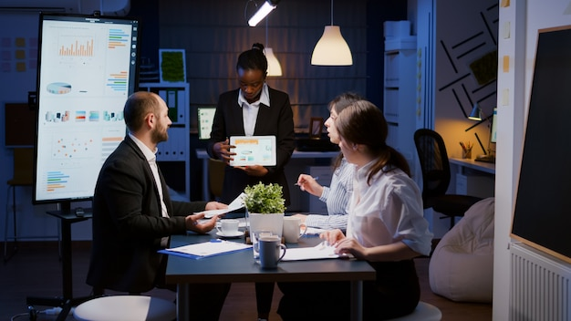 Erschöpfter workaholic-afroamerikaner, der finanzdiagramme mit tablet-überarbeitung im unternehmen zeigt