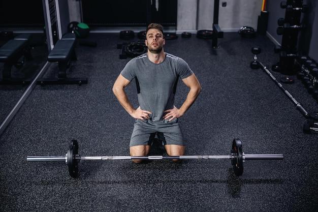 Erschöpfung im training. sportler in sportkleidung pausiert zwischen den übungen. er hält die hände in den hüften und sitzt auf den füßen hinter einer bar mitten im sportzentrum. tabatha-training, cross-fit,