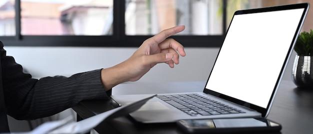 Erschossener geschäftsmann, der auf den bildschirm des laptop-computers zeigt.