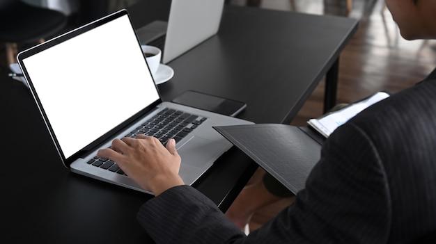 Erschossener geschäftsmann, der dokument hält und mit laptop arbeitet.