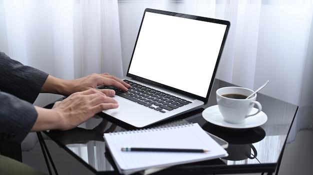 Erschossener geschäftsmann, der in seinem zimmer sitzt und mit laptop arbeitet.