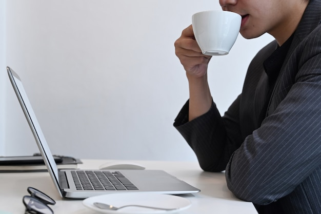 Erschossener geschäftsmann, der kaffee trinkt und e-mails auf laptop-computer liest.