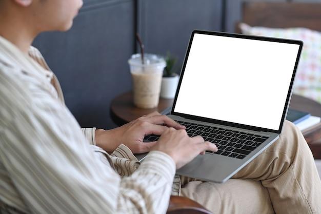 Erschossener junger mann, der im café sitzt und mit laptop-computer arbeitet.