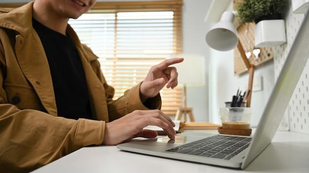 Erschossener lächelnder mann, der zu hause laptop-computer verwendet.