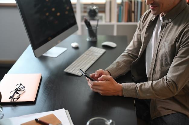 Erschossener mann, der an seinem arbeitsplatz sitzt und ein smartphone benutzt.