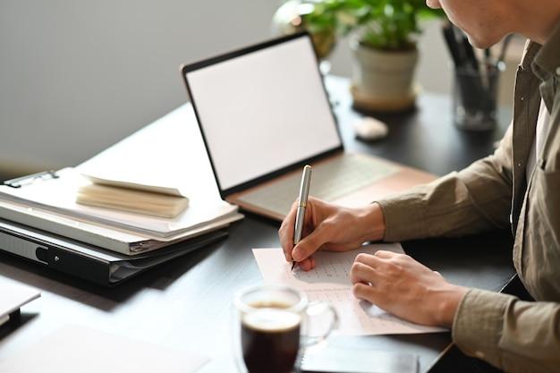 Erschossener mann, der vor laptop-computer sitzt und notizen auf dem notebook macht.
