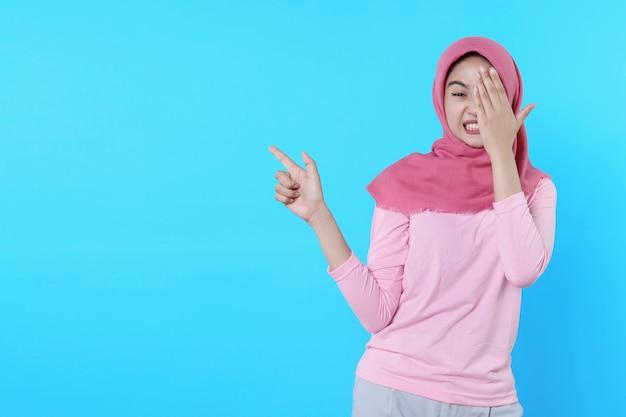 Erschrecken sie asiatische frau mit ihrem finger, der isoliert auf hellblauem hintergrund zeigt, der hijab mit rosa t-shirt trägt