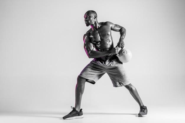 Erschrecken sie nicht. junge afroamerikanische bodybuilderausbildung über grauem studiohintergrund. muskulöses einzelnes männliches model in sportbekleidung mit dem gewicht. konzept von sport, bodybuilding, gesundem lebensstil.
