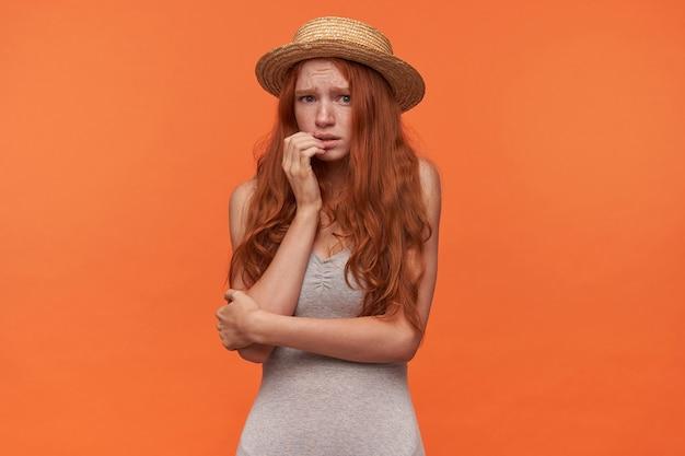 Erschreckte schöne junge rothaarige frau mit gewelltem londem haar, das graues hemd und strohhut trägt, hand auf ihrem gesicht hält und zur kamera erschrocken schaut und über orange hintergrund aufwirft