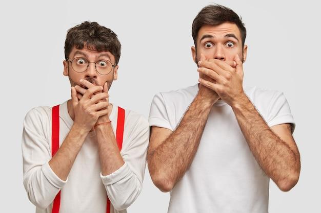 Erschrocken bedecken zwei junge männer den mund mit handflächen, versuchen stumm zu sein und tragen weiße kleidung
