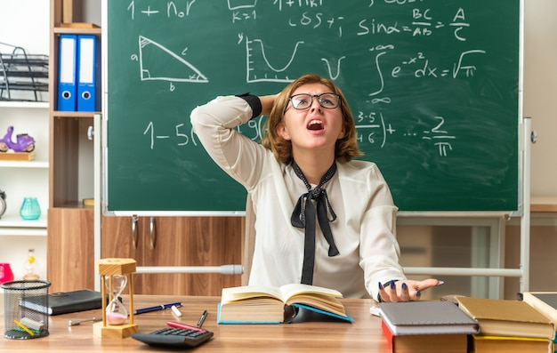 Erschrocken, junge lehrerin mit brille aufzublicken, sitzt am tisch mit schulwerkzeugen, die im klassenzimmer die hand auf den kopf legen