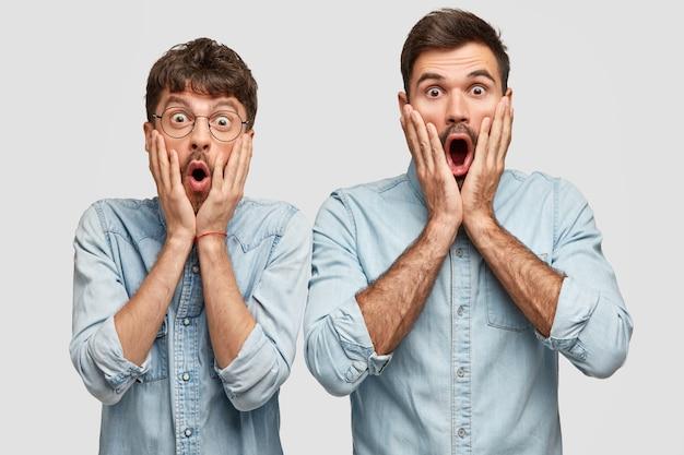 Erschrocken zwei gleichaltrige männer, die in die kamera starren, die wangen berühren und von hohen preisen geschockt sind, während sie zusammen einkaufen gehen