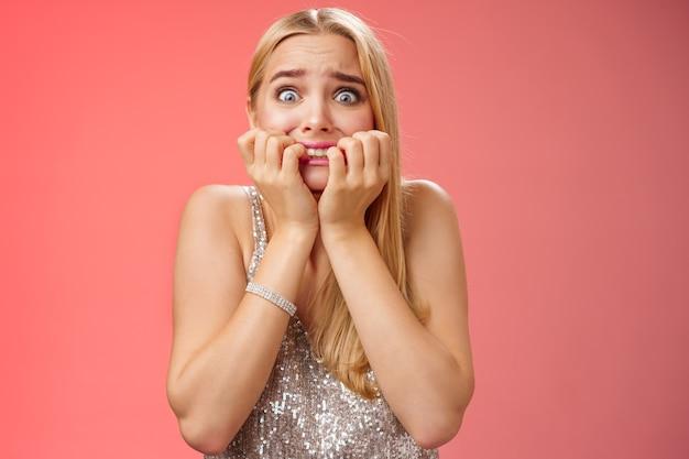 Erschrockene angst in panik geratene junge süße blonde frau, die nägel beißt pop augen erschrockener kamerablick erschrocken fassungslos sprachlos starren nach vorne stehenden roten hintergrund keuchend zitternde angst.