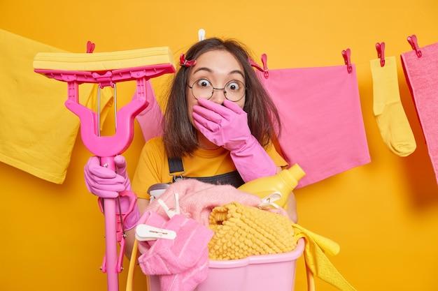 Erschrockene brünette asiatische haushälterin bedeckt den mund mit handposen gegen gewaschene kleidung, die an der wäscheleine hängt, hält mop macht die reinigung des neuen hauses. hauswirtschafts- und hausarbeitskonzept