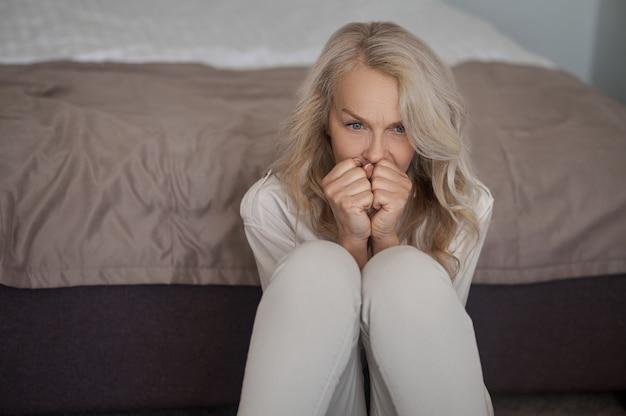 Erschrockene ernsthafte depressive blonde reife kaukasische frau, die mit ihren fäusten umklammert am bett sitzt