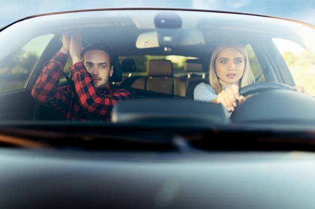 Erschrockene frau und ausbilder im auto, vorderansicht, fahrschule. mann, der dame beibringt, fahrzeug zu fahren. führerscheinausbildung, ein unfall
