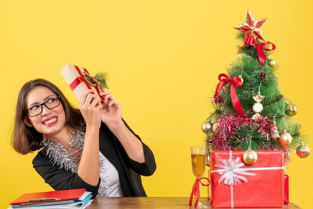 Erschrockene geschäftsdame im anzug mit brille, die ihr geschenk hält und an einem tisch mit einem weihnachtsbaum darauf im büro sitzt
