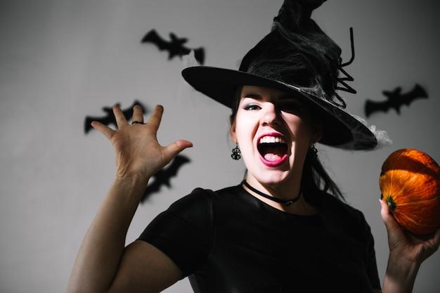 Erschrockene hexe mit kürbis