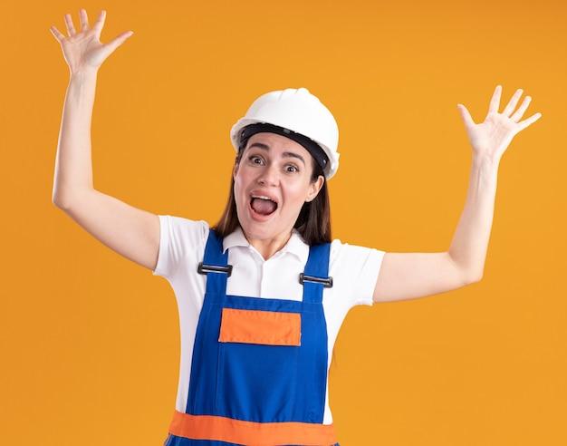 Erschrockene junge baumeisterin in uniform, die hände lokalisiert auf orange wand hebt