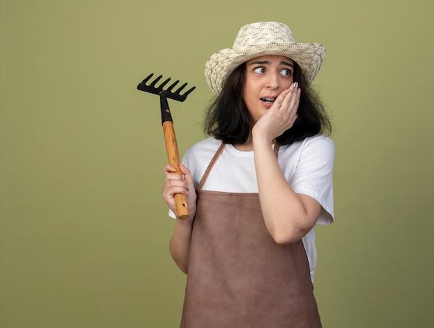 Erschrockene junge brünette gärtnerin in uniform, die gartenhut trägt, legt hand auf gesicht und hält rechen, der seite betrachtet, die auf olivgrüner wand lokalisiert wird