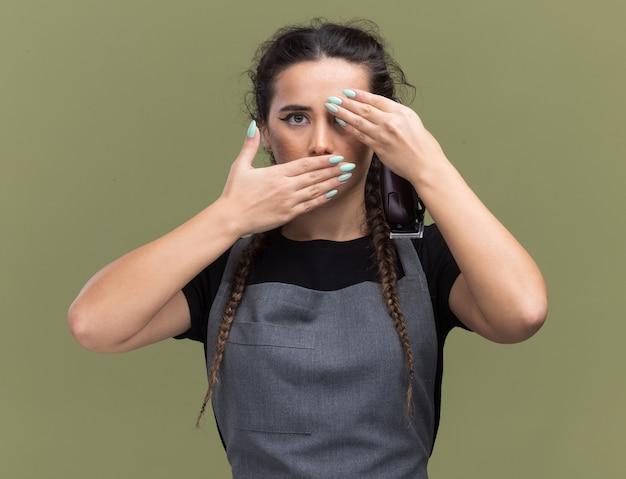 Erschrockene junge friseurin in uniform, die haarschneidemaschinen hält, bedeckte augen und mund mit den händen isoliert auf olivgrüner wand