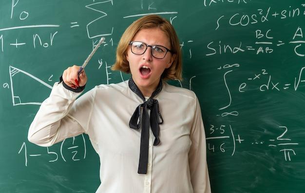 Erschrockene junge lehrerin mit brille, die vor der tafel steht und einen zeigerstock im klassenzimmer hält holding