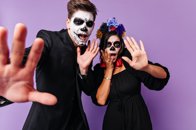 Erschrockene junge leute in halloween-kleidung, die zusammen auf lila hintergrund stehen. innenfoto eines begeisterten europäischen paares, das in muertos-kostümen herumalbert.