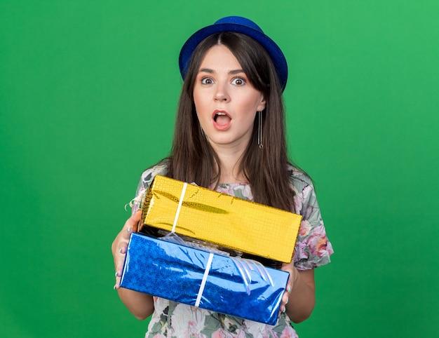 Erschrockene junge schöne frau mit partyhut, die geschenkboxen isoliert auf grüner wand hält