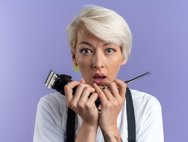 Erschrockene junge schöne friseurin in uniform, die eine schere mit haarschneidemaschinen auf blauem hintergrund hält