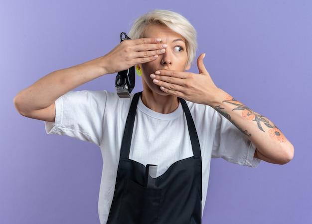 Erschrockene junge schöne friseurin in uniform, die haarschneidemaschinen hält, bedeckte augen und mund einzeln auf blauem hintergrund