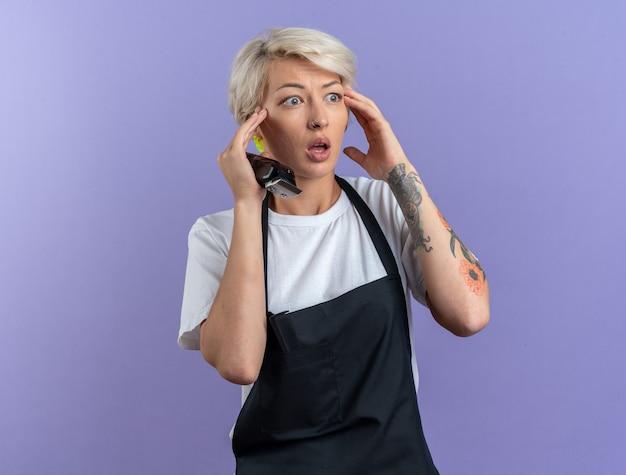 Erschrockene junge schöne friseurin in uniform, die haarschneidemaschinen hält, die die hände auf das gesicht legen, isoliert auf blauem hintergrund