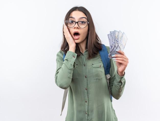 Erschrockene junge schulfrau mit brille mit rucksack, die bargeld hält und hand auf die wange legt