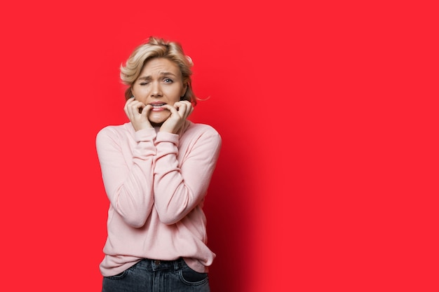 Erschrockene kaukasische frau mit blonden haaren, die finger auf einer roten wand mit kopienraum beißen