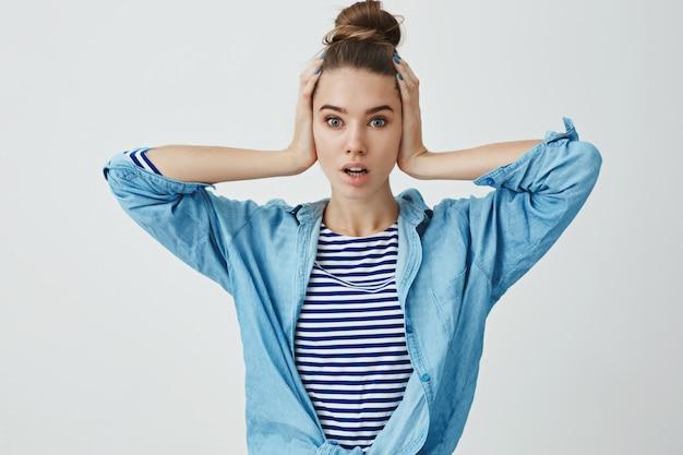 Erschrockene teenagerfrau mit händen auf dem kopf
