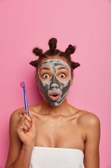 Erschrockene, verängstigte frau starrt mit verwaschenen augen, hält die zahnbürste, putzt die zähne, nachdem sie die schönheitsmaske vom gesicht entfernt hat, kümmert sich um schönheit und hygiene und trägt ein badetuch über dem nackten körper
