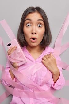 Erschrockene, verängstigte junge asiatin starrt verwanzte augen auf die mit klebebändern umwickelte kamera, die das mobiltelefon hält, und erfährt, dass schockierende nachrichten eine schlechte nachricht erhalten