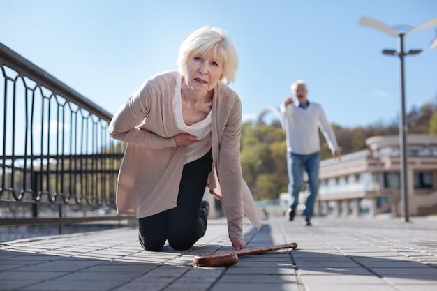 Erschrockene verwirrte alte frau, die sich ausruht und herzinfarkt fühlt, während alter mann läuft, um ihr zu helfen