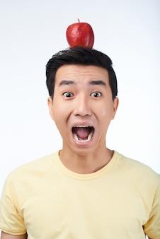 Erschrockener asiatischer mann mit rotem apple